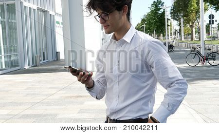 Handsome trendy man wearing white shirt standing and looking down at a cell phone that he is holding, outdoor in city setting