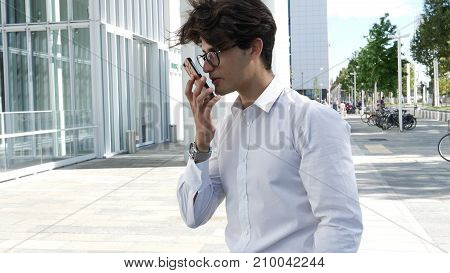 Handsome trendy man wearing white shirt standing and recording voice message on cell phone that he is holding, outdoor in city setting