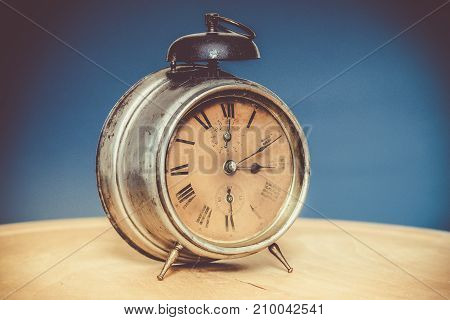 Vintage alarm clock on wooden table blue background deliberately grainy