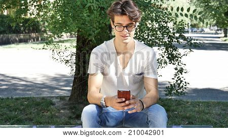 Handsome young man wearing white t-shirt and glasses sitting and typing on cell phone, looking down at smartphone that he is holding, outdoor