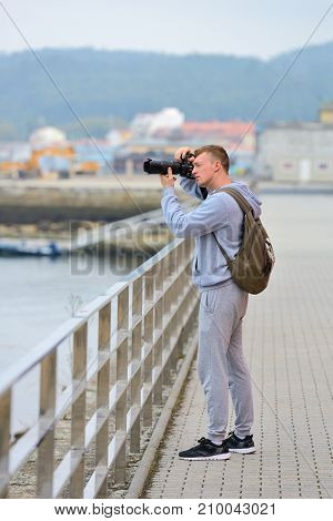 young man takes pictures of the sea from the waterfront