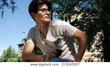 Handsome young man wearing white t-shirt and glasses sitting and holding a cell phone in his hands, outdoor