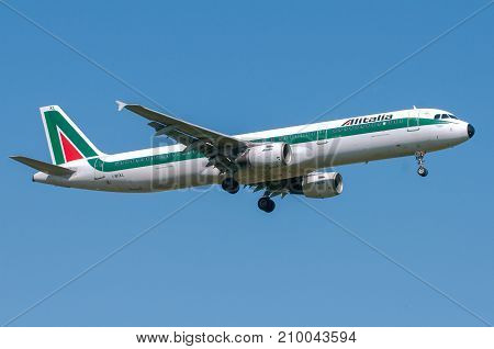 London, UK, April 9th 2011: 2-engines Airbus A321 of Alitalia italian national carrier landing at Heathrow airport.