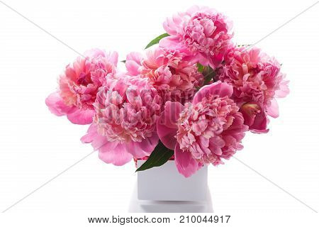 bouquet of pink peonies in a wicker vase on a white background