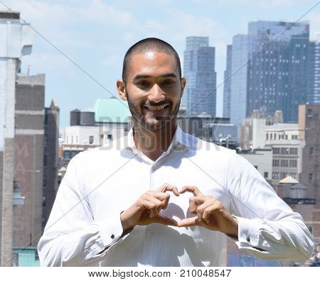 Handsome Latino Man Outside Making Heart Shape