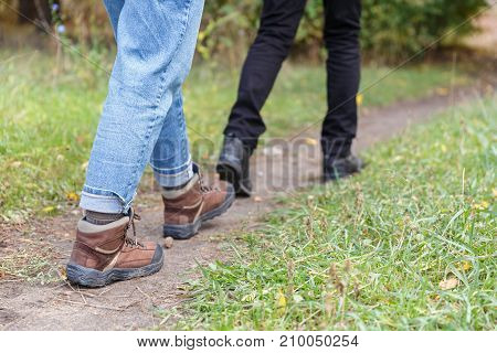The legs of a man and a woman in the forest. Hiking, traveling. Close-up.