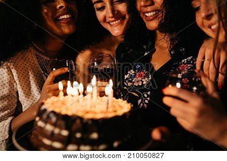 Happy girlfriends celebrating a birthday, holding a cake with lit candles