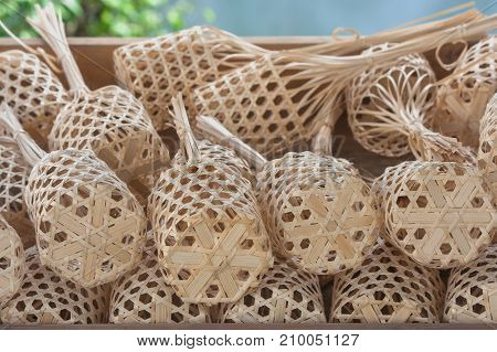 Close up stack or row of brown round bamboo market in wooden tray.