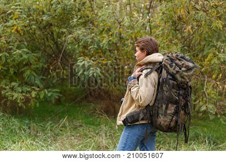 A young tourist girl, with a short haircut, walks through the forest with a large backpack on her back.