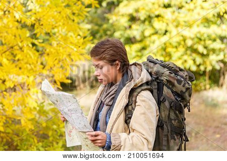 Girl tourist with short haircut and backpack, looking at map in autumn forest. The concept of leisure, travel.