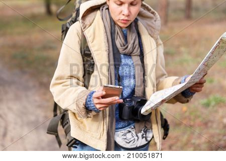 A young girl with a short haircut in the woods is looking for a road map and using the phone. Close-up.