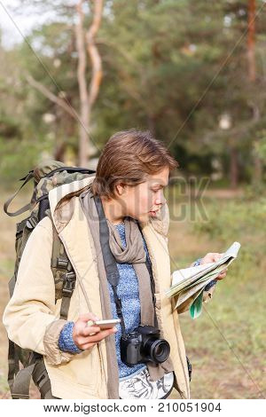 A young tourist girl with a short haircut in the woods is looking for a road map and using a phone. The concept of travel.