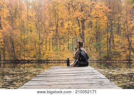 Girl enjoys rest and drinks hot coffee near the lake at nature park on gold autumn day. Young female hiker with backpack sits at riverbank drinks coffee and looks at beautiful indian summer scenery