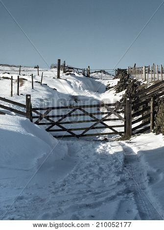 snow covered country lane with wooden gates and surrounding fields and moors