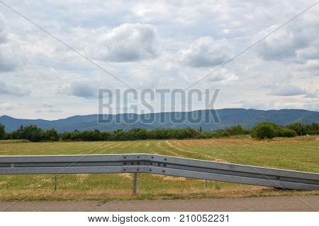 View of a landscape and sky behind a road safety barrier