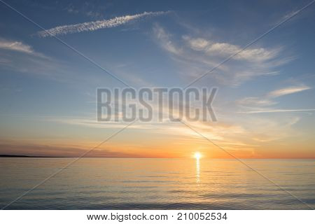 Evening sunlight on coast pink clouds blue sky reflection on water. Beach in summer. Seaside natural environment. Shore in Kesselaid small island in Estonia. Nature Reserve in North Europe