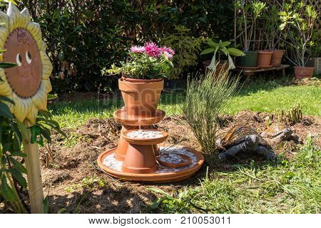 selfmade fountains made of clay pots and pebbles - water play and decoration