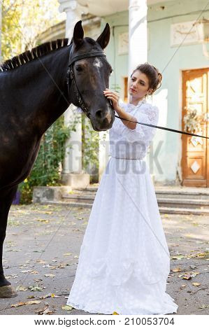 Portrait of a beautiful bride, brunette and horse. In full growth. The concept of a wedding.
