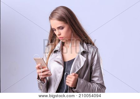 Young girl listening to music with a smartphone on a gray background