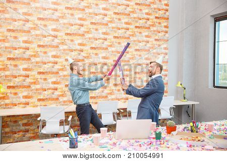 In the office at a corporate party, men are fooled with sticks from under confetti. The concept of a holiday, work.