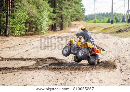 An Atv Quadbike Driver Drifts And Stunts On A Sand Rough Terrain Near Forest, Turns On A Two Wheels