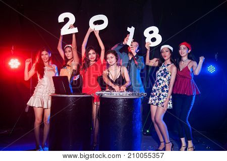 Group of people dancing at night club with Santa hat Christmas holidays party friendship relaxing celebrating new year 2018.