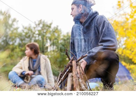 Couple relaxing in the forest. A loving couple is sitting in front of the tent. The concept of adventure. Tourism. Field fire.