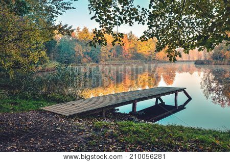 Beautiful autumn landscape. Wooden pier and colorful trees on the lake.