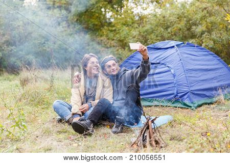 Young couple photographed on the phone in the autumn forest. Against the background of tents and trees. The concept of leisure, travel.