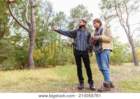Young travelers as a couple pointing to the target in the autumn forest. Close-up. The girl with a short haircut.