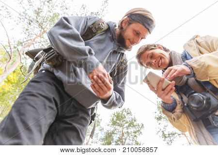 Young couple looking at photos on mobile phone. Happy young people in a park or in the forest using a smartphone