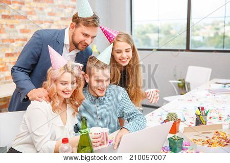 Business people working during a holiday at the computer. On the table are drinks, pizza and confetti. View from above.