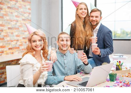 Business people working during a holiday at the computer. Pose. On the table are drinks, pizza and confetti. View from above.
