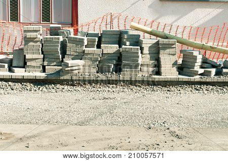 Paving stone tiles prepared to pave over gravel road on the street reconstruction site