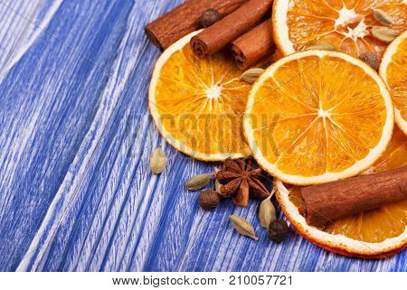 Dry slices of orange, cinnamon, allspice and cardamom on blue wooden background