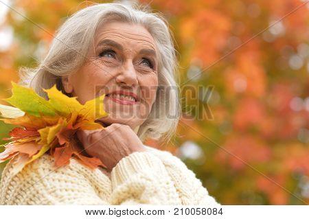 Happy senior woman resting in autumnal park