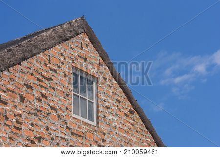 Window on brown brick wall and wooden roof in vintage style with blue sky background.