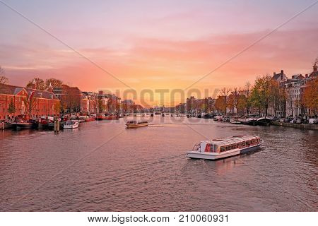 City scenic from Amsterdam in the Netherlands at the river Amstel at twilight