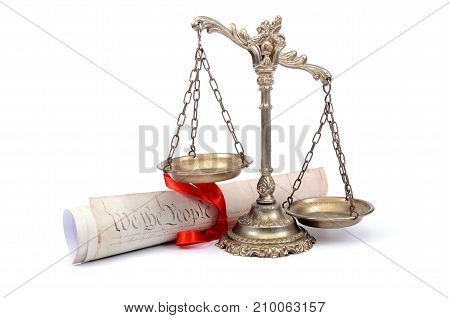 Scales of justice and US Constitution on the white background.