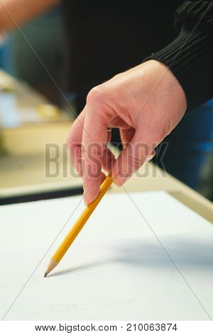 Artist's hand close-up during a painting lesson. The artist sketches a pencil in a school of painting, preparing a blank canvas for the creation of a painting. concept of the school of painting.