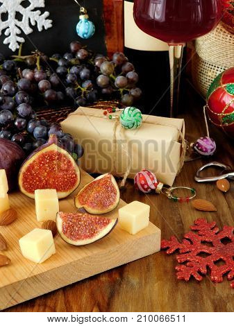 Cheese and figs on a wooden board, red wine in a glass, grape and Christmas attributes around. Christmas table laying