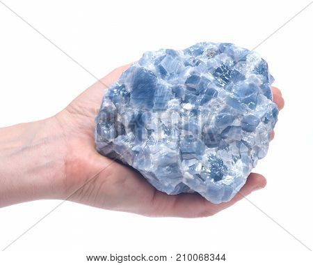 Woman's hand holding raw blue calcite cluster isolated on white background
