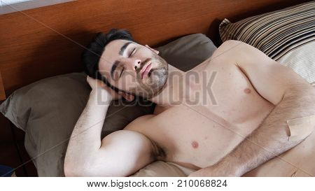 Young Handsome Shirtless Man Sleeping, Lying in Bed in the Morning