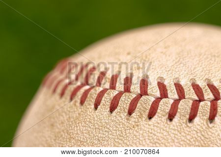 Close up of a baseball on green background