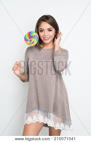 Teen girl holding a lollipop on white background