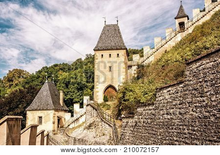 Gothic castle Karlstejn in Czech republic. Ancient architecture. Travel destination. Walls and turrets. Yellow photo filter.