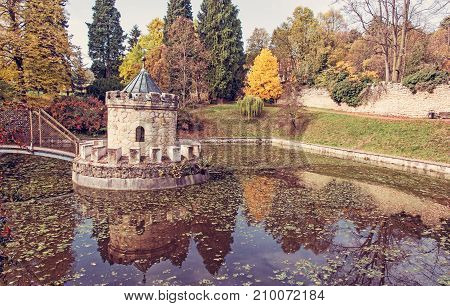 Turret in Bojnice autumn park lake and colorful trees. Slovak republic. Seasonal natural scene with beautiful pond. Red photo filter.