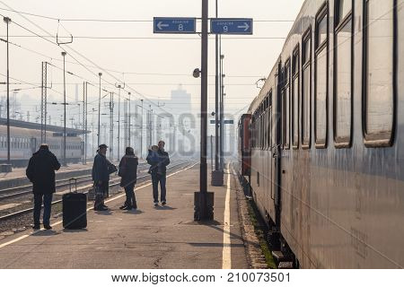 BELGRADE SERBIA - FEBRUARY 14 2015: Passengers waiting to board a train on the platform of Belgrade main train station during a sunny afternoon