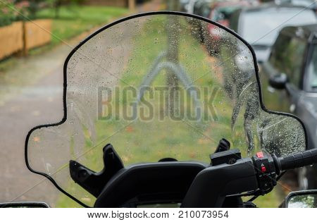 Wet windshield of a scooter after rain