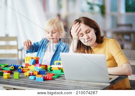 Adorable little boy playing with colorful plastic construction blocks while his mother working on her laptop. Childcare and work concept poster